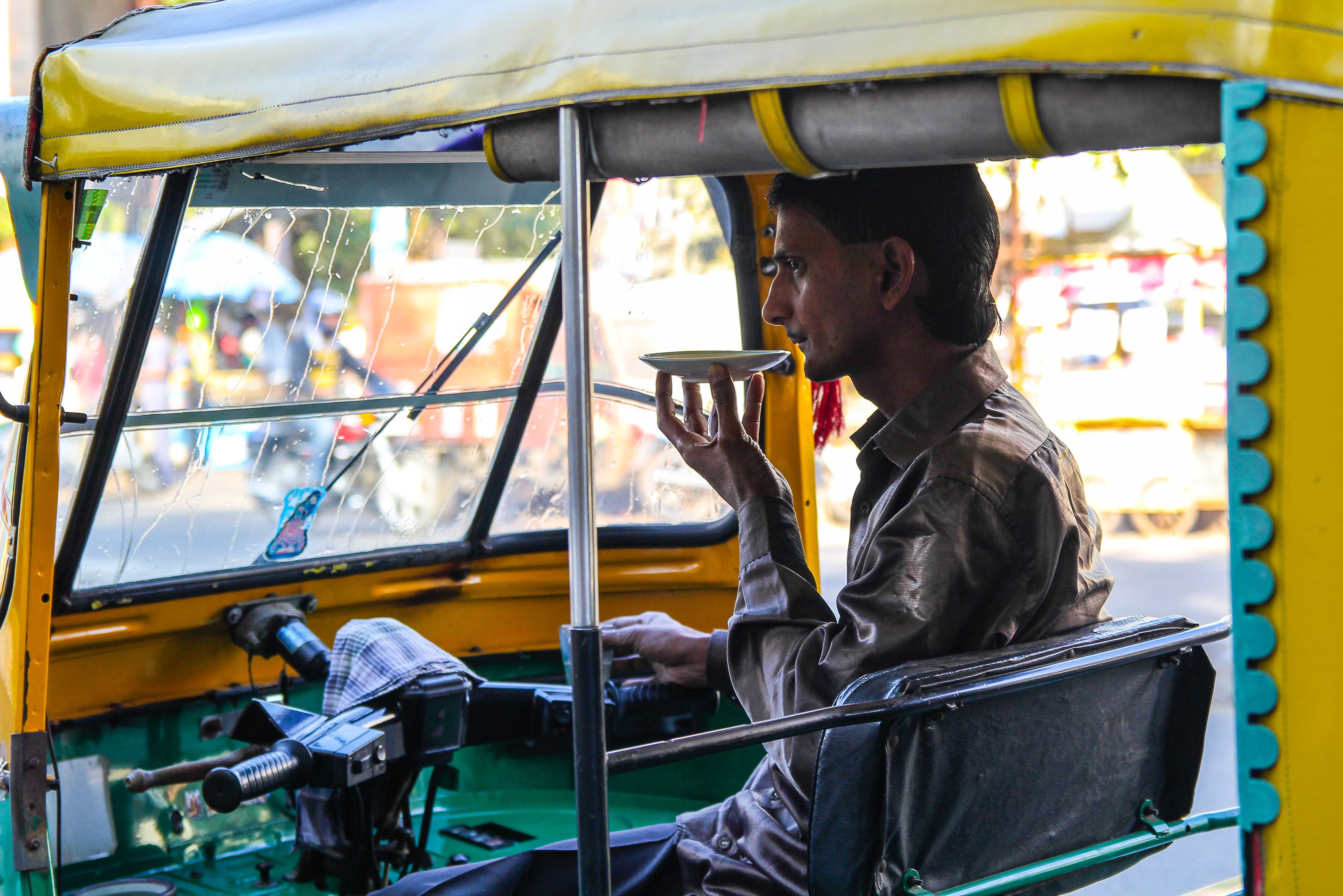 An auto-rickshaw driver sips Bharat Bhai's chai out of a saucer.