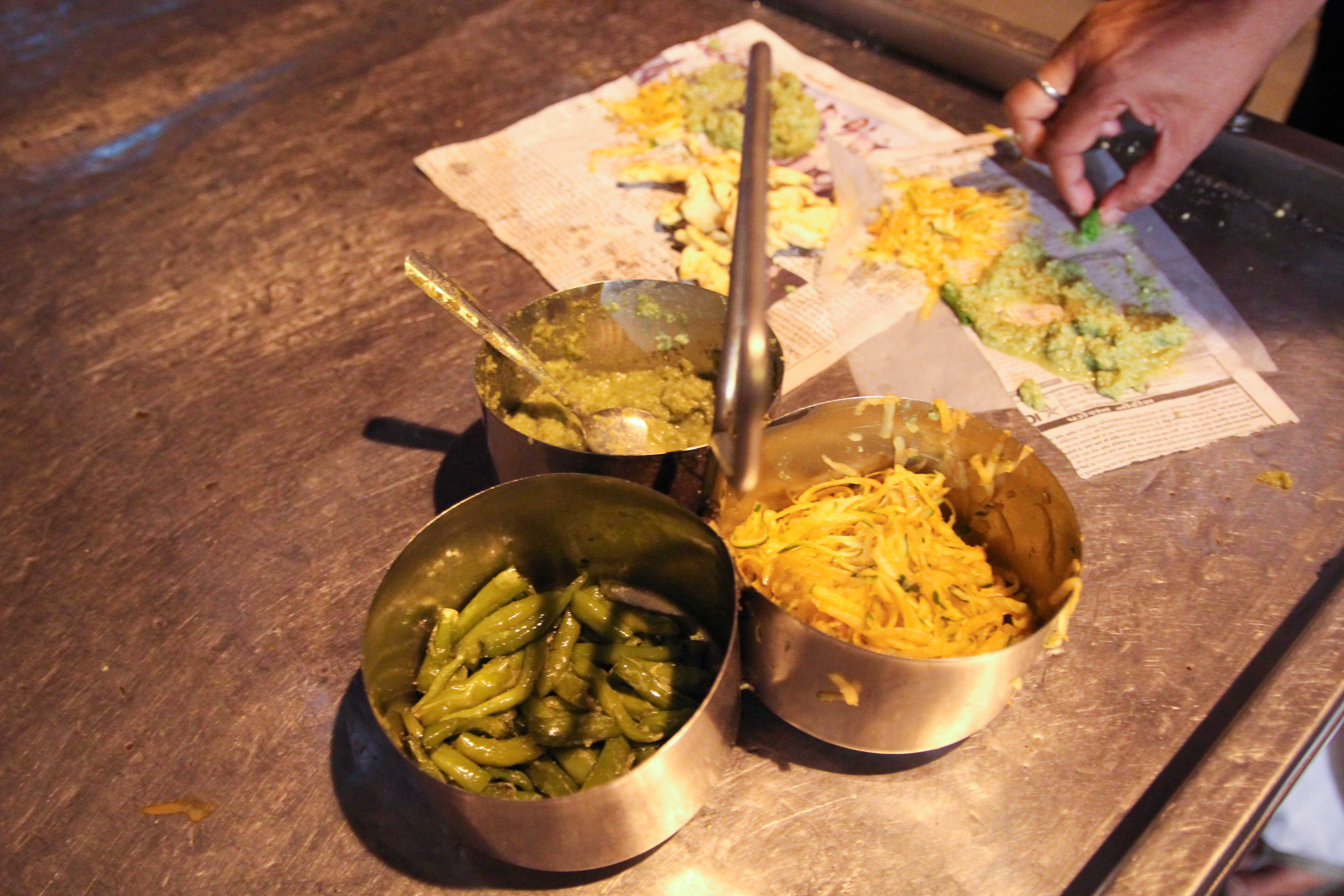 Gathiya, a typical deep-fried Gujarati snack, served with chilis, mint chutney and raw papaya slaw.
