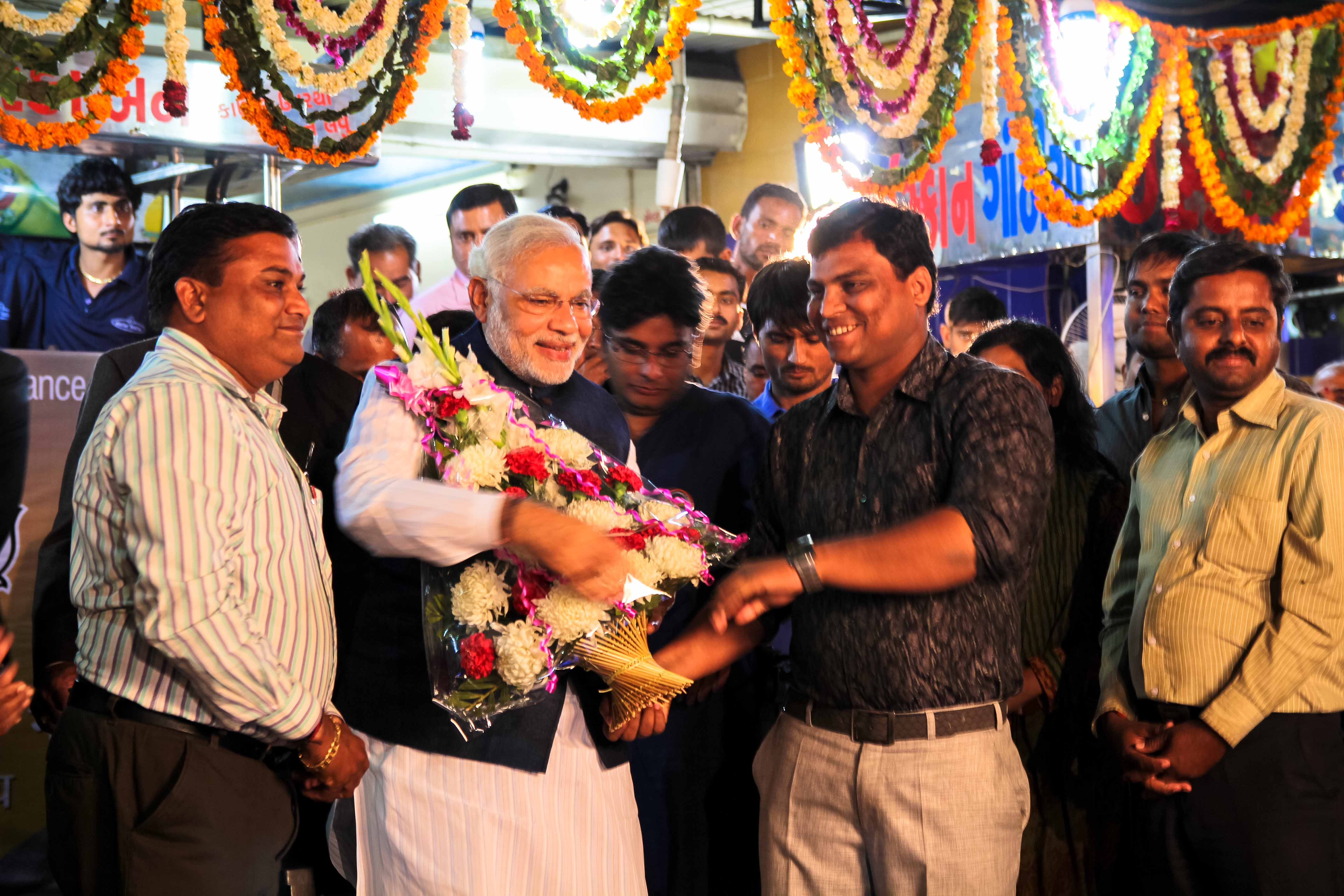 Iscon Ganthiya owner Mandeep Patel presented Narendra Modi with a garland of flowers in addition to cups of tea at the Chai Pe Charcha in Ahmedabad, Gujarat on Feb. 12, 2014.