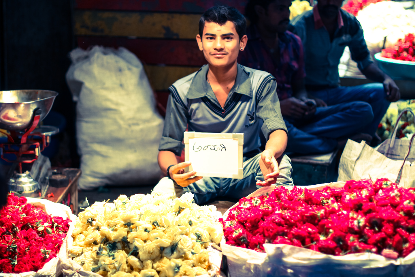 Eighteen-year-old Sashikumar sells roses in Bangalore's City Market. He cannot leave his merchandise, so he relies on the chai wallahs who weave in and out of piles of flowers to bring him chai throughout the day.