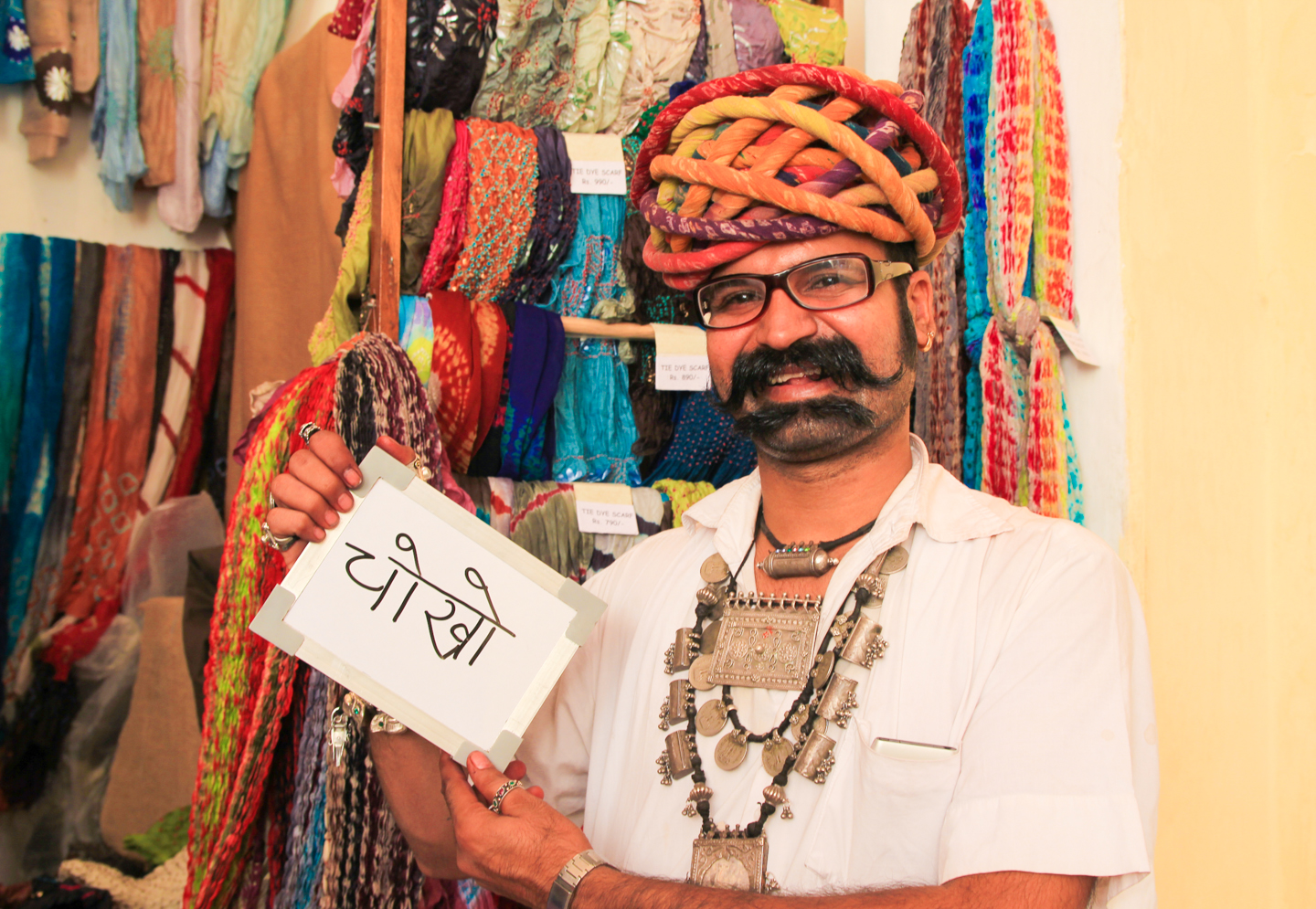 Ishwar Devani has been selling handmade scarves in Jodhpur's Mehrangarh Fort for 14 years. He learned the business from his father. 'Every day I play with colors. Look at my hands. You can see from my hands that this is my family business.'